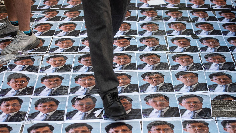 資料圖片:2019年9月26日,何君堯照片被鋪在地上任人踩。(法新社)