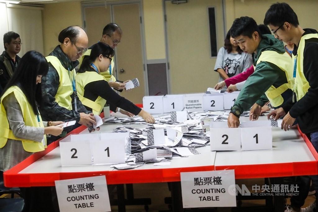 香港近日抗爭情勢逐漸趨緩,24日區議會選舉如期舉行,晚間10時30分結束投票後進行點票作業,灣仔一家投票站工作人員25日淩晨仔細清點選票。中央社記者吳家昇攝 108年11月25日