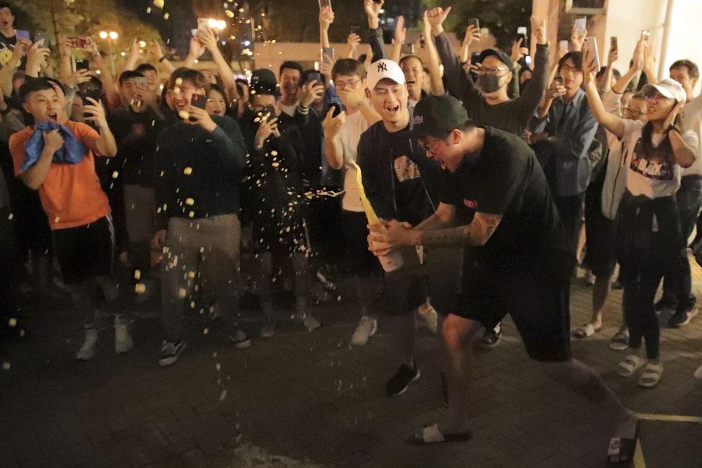 香港泛民主派在地方區議會選舉中大獲全勝,親中建製派則大敗。圖為建製派候選人何君堯確定落選後,泛民派支持者在街頭開香檳慶祝。(美聯社)