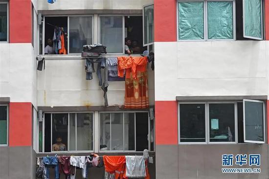 4月6日,在新加坡西雅卓源外籍劳工宿舍,几名外籍劳工从宿舍楼中向外张望。